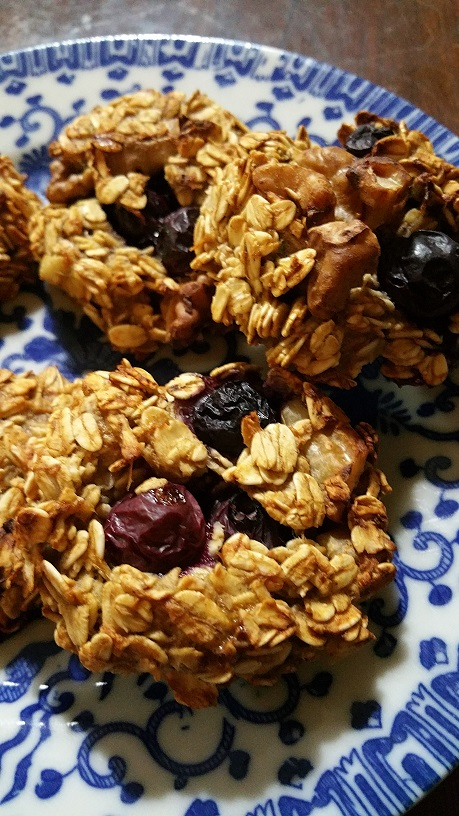 Banana-oatmeal cookies with walnuts and blueberries on a blue plate.