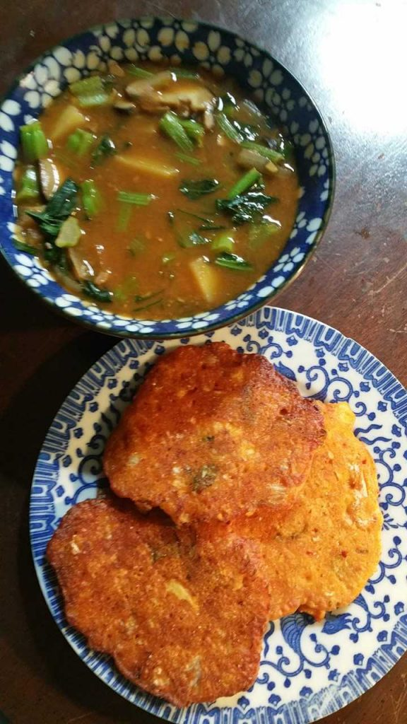 Bowl of deanjang (korean soybean stew) with lots of veggies, and plate of kimchi pancakes.