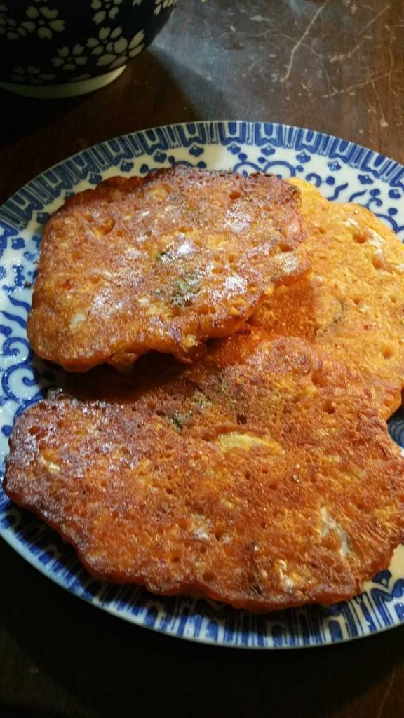 3 small kimchi pancakes fried to golden brown perfection on a small blue plate.