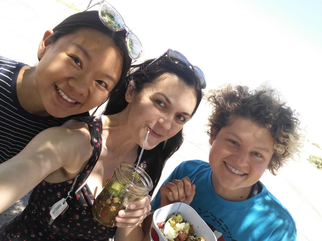 Self-indulgent memory lane selfie of myself with two friends, eating made-ahead cold bean salad off the back of my car midway through a road trip.