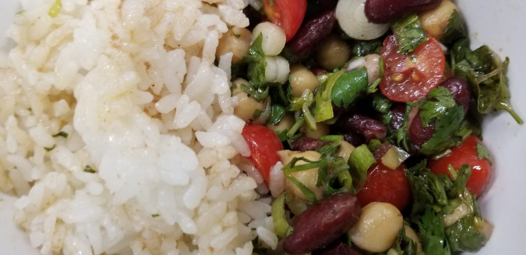 """This is an image of cold bean salad paired with white rice. The caption reads: The human body needs 20 amino-acids to form proteins that help with a variety of body functions. Nine of these are """"essential,"""" meaning that the body can't produce them and must obtain them from food. Apart from meat sources, which contain all of the essential amino acids, the easiest way to ensure a healthy supply of these is to eat plant-based foods that complement each other to form complete sets of essential amino acids. Of these complements, beans and rice are a world-wide classic."""