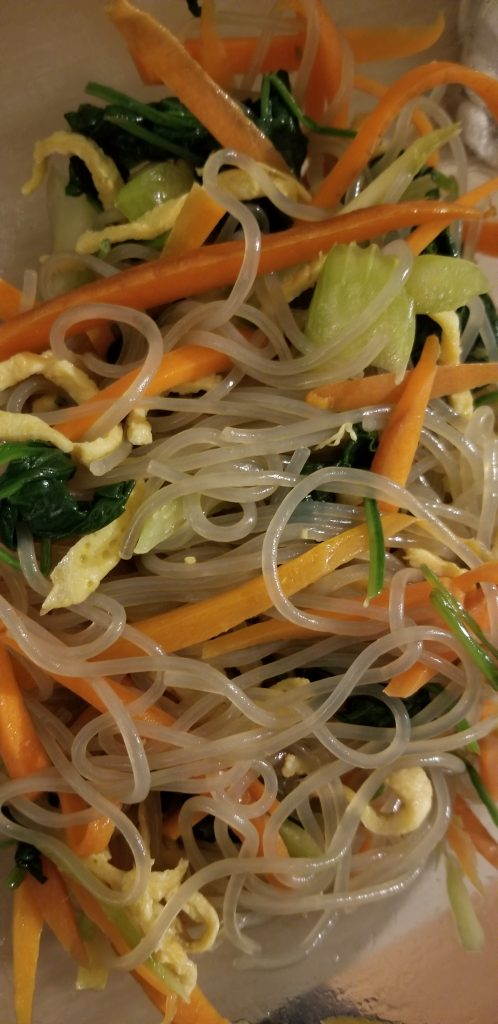 close up of sweet potato noodles with eggs, spinach, carrot, and scallion